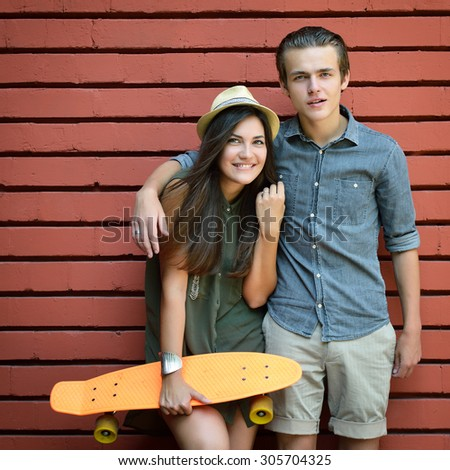 Young couple posing with penny board summer outdoor against red brick wall. Urban lifestyle, happiness, joy, friends, teenage, first love concept. Image toned and noise added. - stock photo