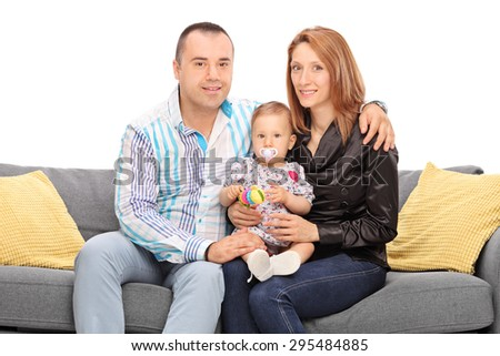 Young couple posing with their baby daughter seated on a sofa isolated on white background - stock photo