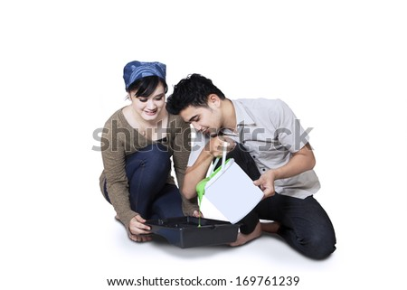 Young couple pouring paint into tray. isolated on white