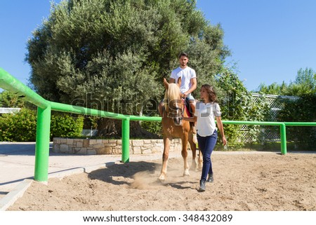 Young couple practices horseback riding lessons with a brown-blond purebred mare in the riding club arena. - stock photo
