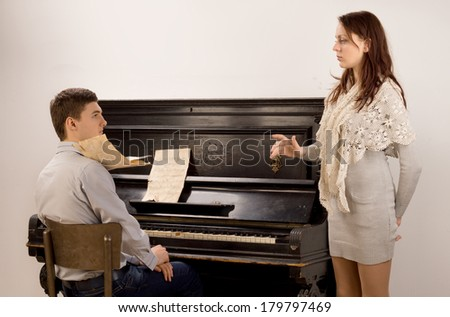Young couple practicing a classical duet pausing for a discussion as the pretty female vocalist raises an issue with the young male pianist - stock photo