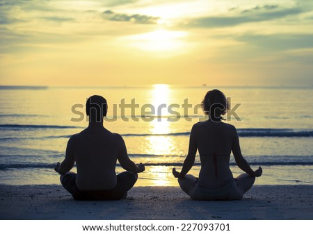 Young couple practicing yoga in the lotus position on the ocean beach during sunset. Cross-process photo style. - stock photo
