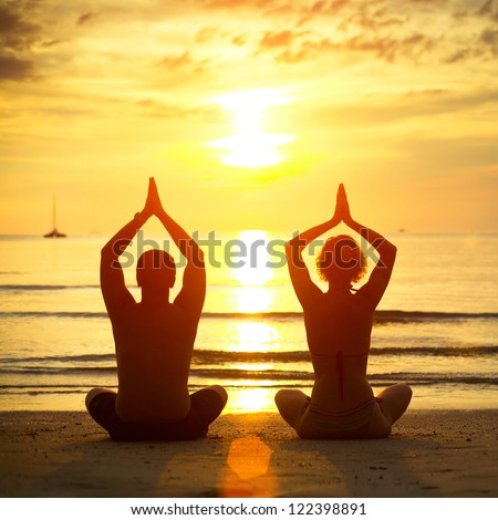 Young couple practicing yoga on the beach at sunset - stock photo
