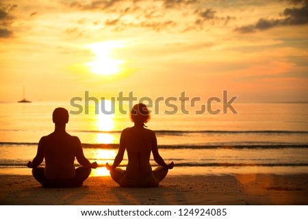 Young couple practicing yoga on the beach at sunset. - stock photo