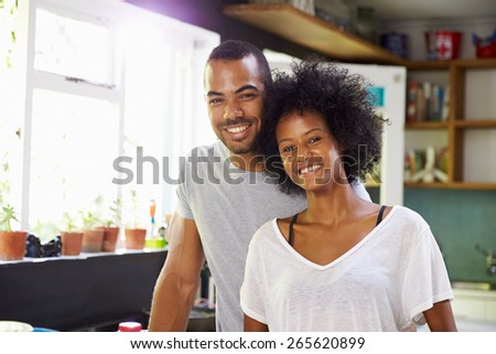 Young Couple Preparing Breakfast In Kitchen Together - stock photo