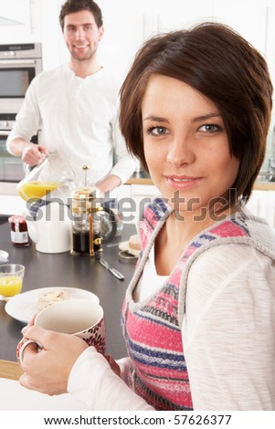 Young Couple Preparing Breakfast In Modern Kitchen - stock photo