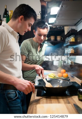 Young couple preparing dinner in theirs kitchen - stock photo