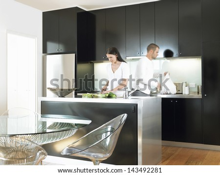 Young couple preparing food in modern kitchen - stock photo