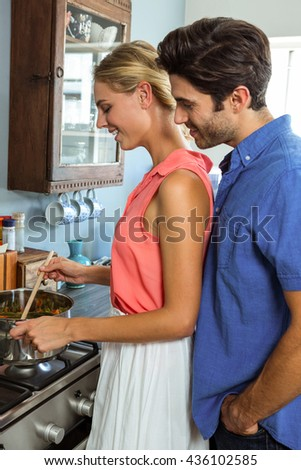 Young couple preparing food together in the kitchen at home