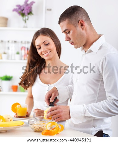 Young couple preparing orange juice in their kitchen.