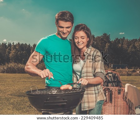 Young couple preparing sausages on a grill outdoors  - stock photo