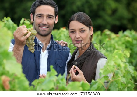 young couple proud of their vineyard - stock photo