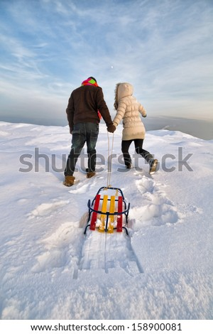 Young couple pulling up a sled at snow - stock photo