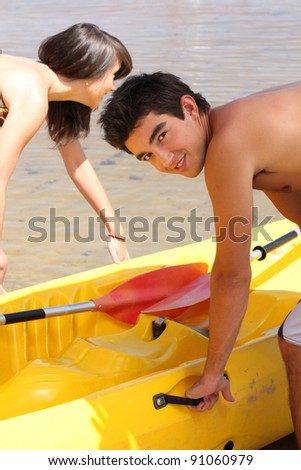 Young couple putting a canoe in the water - stock photo