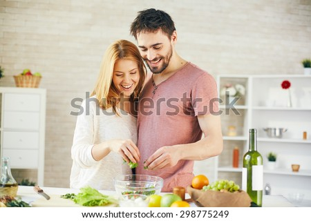 Young couple putting cut lettuce into bowl - stock photo