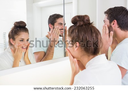 Young couple putting on face cream at home in the bathroom - stock photo