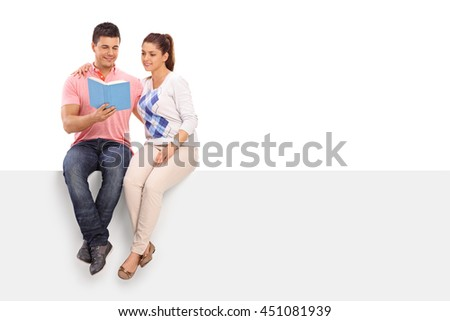 Young couple reading a book together seated on a blank panel isolated on white background