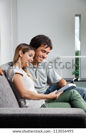 Young couple reading a book together while sitting on sofa at home - stock photo
