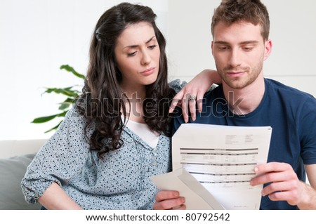 Young couple reading a financial bill or letter with worried expressions at home - stock photo