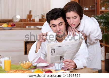 Young couple reading a newspaper at breakfast - stock photo