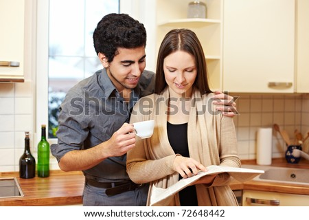 Young couple reading a newspaper together in the kitchen