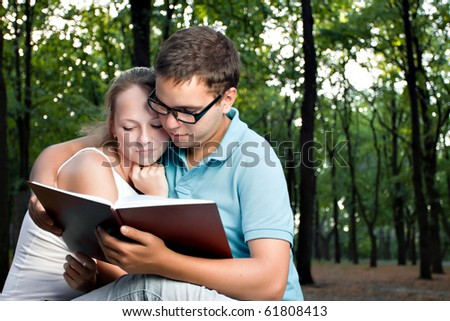young couple reading book in the park - stock photo