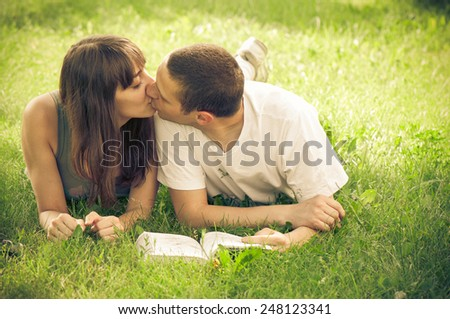 Young couple reading book outdoor