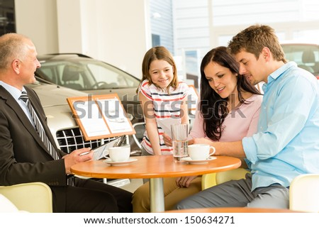 Young couple reading contract in car dealership - stock photo