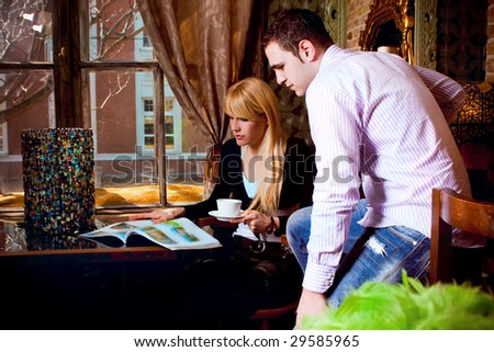 young couple reading magazine in cafe - stock photo