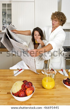 Young couple reading the newspaper together in an unusual way - stock photo