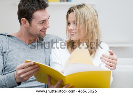 Young couple reading together a magazine and looking each other in their living room at home