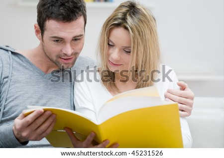Young couple reading together a magazine in their living room at home - stock photo