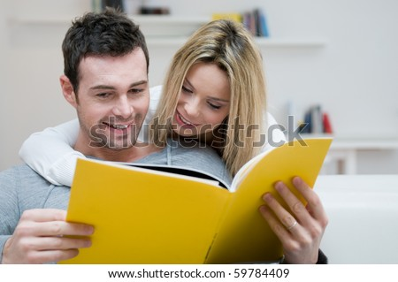 Young couple reading together a magazine in their living room at home