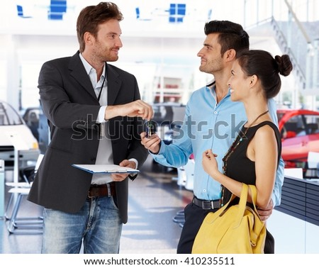 Young couple receiving car keys from agent in car showroom. - stock photo