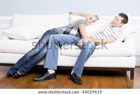 Young couple recline on a white sofa with the young woman lying on the man with a pillow. Horizontal shot.
