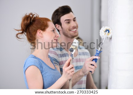 Young couple redecorating at home working as a team as they stand painting a white wall together - stock photo