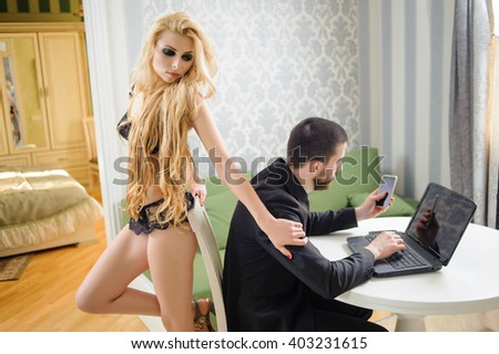 Young couple. Relationship work and lifestyle concept. Handsome man in black suit is working on the laptop and holding cell phone. Woman with blonde hair in black lace lingerie is standing behind him - stock photo