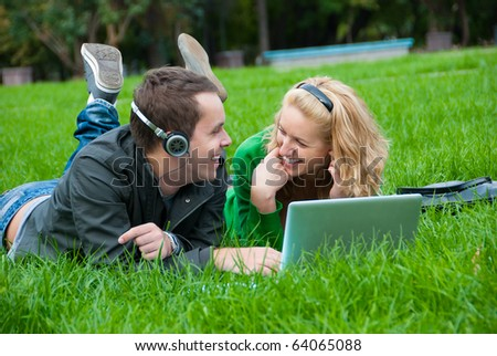 Young couple relax and listen to music from laptop on the grass in the park - stock photo