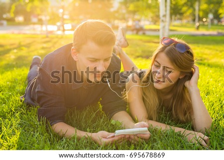 Young couple relax and listen to music on the grass in the park