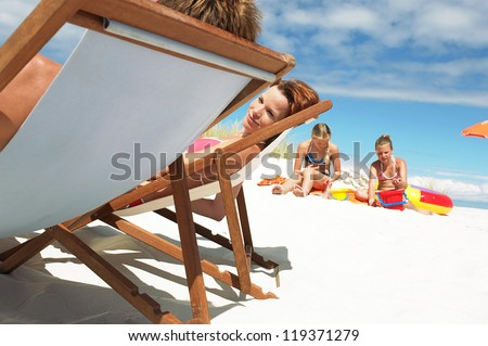 Young couple relax in deck chairs while their small daughters play nearby in the white sand on a summer beach