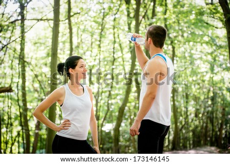 Young couple relaxing after jogging in a forest, man drinking water - stock photo