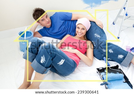 Young couple relaxing after painting a room in their new house against house outline - stock photo