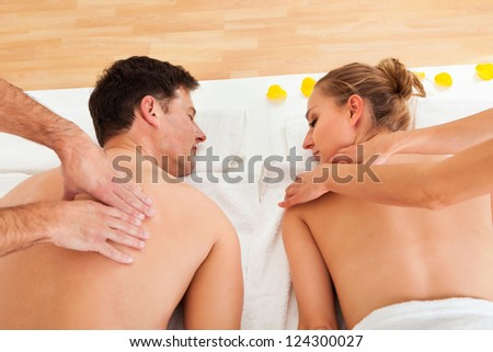 Young couple relaxing and enjoying a joint back massage at a spa and the woman is surrounded by yellow flower petals