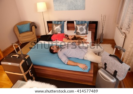 Young couple relaxing in bed in hotel room upon arrival. Luggages around.
