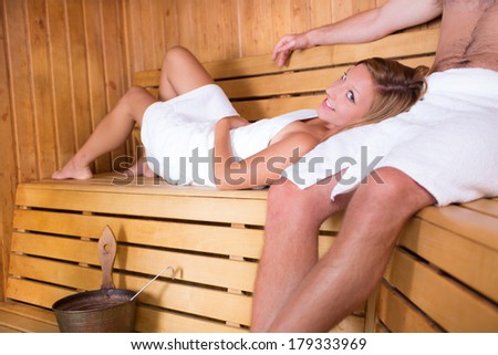 Young couple relaxing in traditional wooden Finnish sauna.