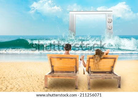 Young couple relaxing lying down on a beach chair and watch tv - stock photo