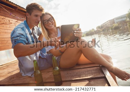 Young Couple Relaxing Near River Using Digital Tablet - stock photo