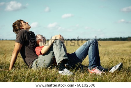 Young couple relaxing on a meadow - stock photo