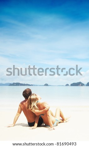 Young couple relaxing on a resort's white sand - stock photo