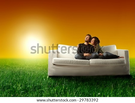 young couple relaxing on a sofa in a grass field - stock photo